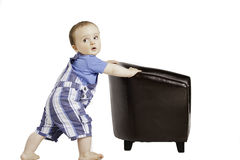 Cute baby pushes a small chair Royalty Free Stock Image