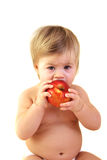 Cute baby with red apple. 1 year old toddler eating apple isolated over white Royalty Free Stock Photography