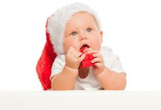 Cute baby in red Christmas hat with small gift box. Cute chubby baby wearing red Christmas hat with small gift box near his mouth on the white background royalty free stock photo