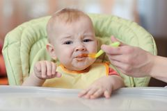 Cute baby boy refusing to eat food from spoon with face dirty of vegetable puree. Royalty Free Stock Images