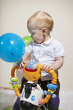 Cute baby riding a new toy Stock Images