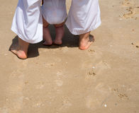 Cute baby`s leg in the sand Stock Images
