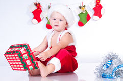 Cute baby Santa Claus with garlands. Stock Photo
