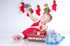 Cute baby Santa Claus looking at the toy. Royalty Free Stock Photos