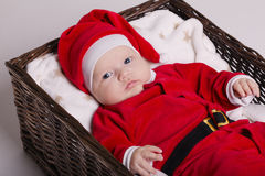 Cute baby with santa costume lying in basket Royalty Free Stock Image