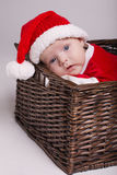 Cute baby with santa costume lying in basket Stock Image