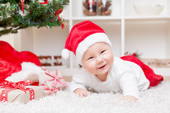 Cute baby in a Santa hat next to Christmas tree with presents Stock Photography