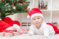 Cute baby in a Santa hat next to Christmas tree with presents Royalty Free Stock Images