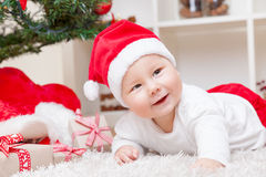 Cute baby in a Santa hat next to Christmas tree with presents Royalty Free Stock Photos
