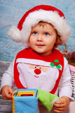 Cute baby in santa hat playing with toys Stock Images