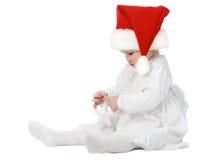Cute baby in Santa's hat. Funny baby girl examining New Year toy Stock Photo