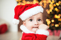 Cute baby in santa suit near xmas tree Royalty Free Stock Image