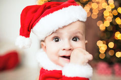 Cute baby in santa suit near xmas tree Stock Images