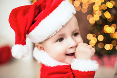 Cute baby in santa suit near xmas tree Royalty Free Stock Photos