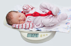 Cute baby on the scales Royalty Free Stock Photography