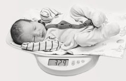 Cute baby on the scales Royalty Free Stock Images