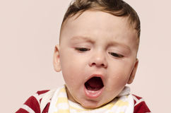 Cute baby screaming refusing to eat baby food. Stock Images