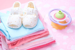 Cute baby shoes for kids on pile of baby clothes. Royalty Free Stock Photo
