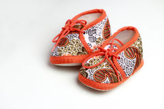 Cute baby shoes. Small baby orange sneakers on a white background.baby shoes Stock Photos