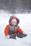 Cute baby sit on fresh snow in park Royalty Free Stock Photos