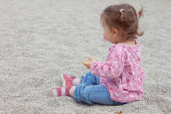 Cute baby sit in gravel Royalty Free Stock Photo