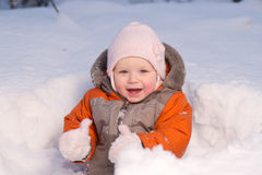 Cute baby sit in snow in forest and dig it Royalty Free Stock Photography