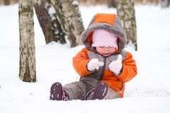 Cute baby sit on snow and play with mittens Stock Images