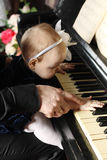 Cute baby sits at knees of father and plays piano Royalty Free Stock Images