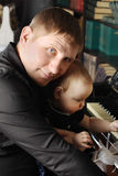 Cute baby sits at knees of her father and touches piano Royalty Free Stock Photos