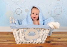 Cute baby sitting in basket with blanket on head Stock Images