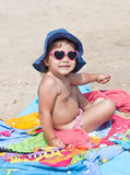 Cute baby sitting on the beach. In sun glasses in the form of hearts stock photography