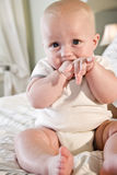 Cute baby sitting on bed with hand in mouth Royalty Free Stock Image