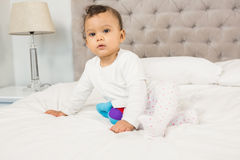 Cute baby sitting on bed Stock Photo