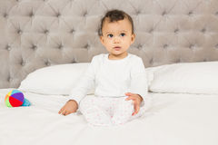 Cute baby sitting on bed Royalty Free Stock Images
