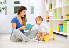 Cute baby sitting on bedpan and listening kid story. With mom stock photos