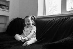 Cute baby is sitting in a black chair at home. Royalty Free Stock Photo