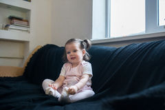 Cute baby is sitting in a black chair at home. Royalty Free Stock Images