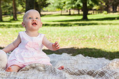 Cute baby sitting on blanket at the park. Full length of a cute baby sitting on blanket at the park Stock Image
