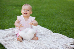 Cute baby sitting on blanket at park. Full length of a cute baby sitting on blanket at the park Stock Photography