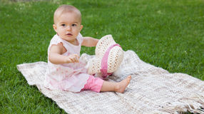Cute baby sitting on blanket at park. Full length of a cute baby sitting on blanket at the park Royalty Free Stock Photo