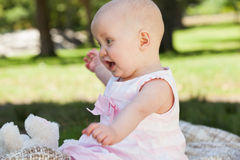 Cute baby sitting on blanket at park. Side view of a cute baby sitting on blanket at the park Royalty Free Stock Images