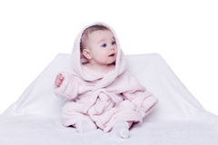 Cute baby sitting on a chair in a pink bathrobe Royalty Free Stock Images