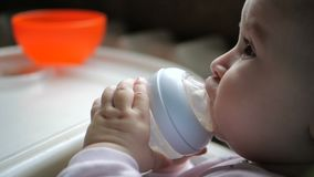 Cute baby sitting and drinking water from a bottle with a dropper in slow motion stock video