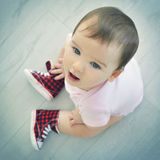 Cute baby sitting on the floor and looking at camera. Top view. Stock Images