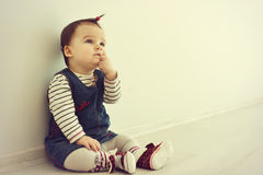 Cute baby sitting on the floor near the wall and thinking. Royalty Free Stock Images