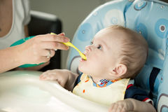 Cute baby sitting in highchair and opening mouth for spoon with. Portrait of cute baby sitting in highchair and opening mouth for spoon with porridge Royalty Free Stock Image