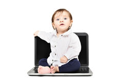 Cute baby sitting on a laptop Stock Photo