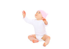 Cute baby sitting looks up on white background Royalty Free Stock Images