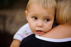 Cute baby sitting on mother hands and looking away. Cute blonde brown-eyed baby sitting on the mother hands and looking away on the blurred background Royalty Free Stock Photos