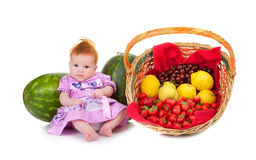 Cute baby sitting next fruit basket Royalty Free Stock Images
